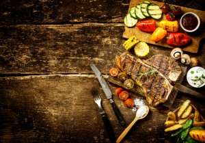 Preparing t-bone steak and roast vegetables in a country kitchen with bell peppers, mushrooms, tomato, potato, mangetout peas, and corn on a rustic wooden table with copyspace