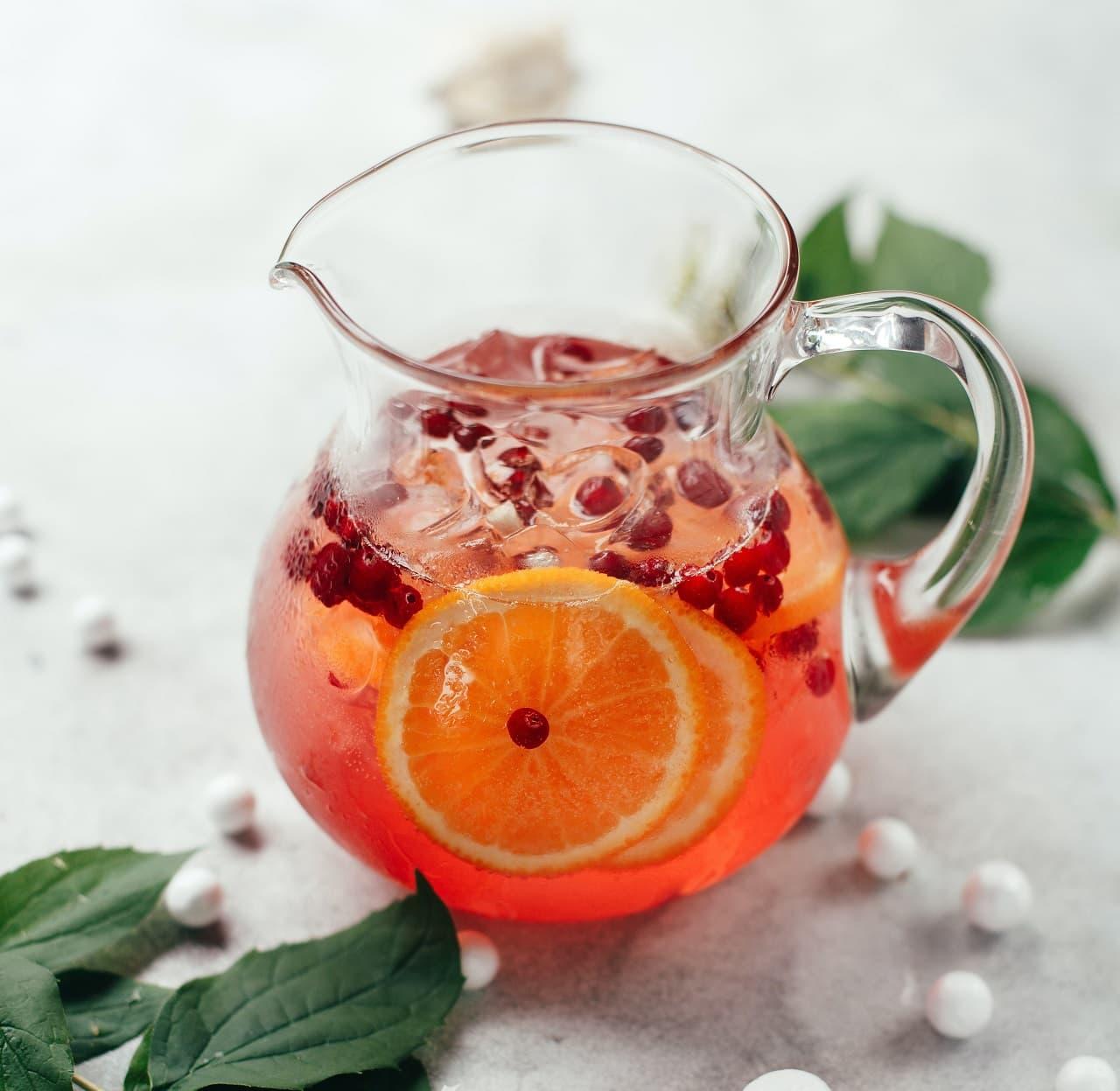 Limonade mit Beeren und Orange in Karaffe